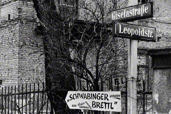 Ein Schild an der Ecke Leopold- und Giselastraße zeigt den Weg zum Schwabinger Brettl Kabarett in München an.