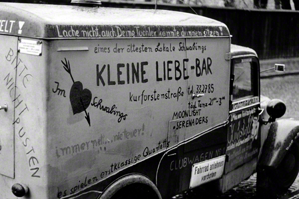 """Werbung für die """"Kleine Liebe Bar"""" auf einem LKW in der Leopoldstraße in München."""