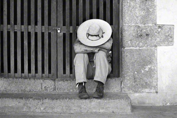 Ein Mann sitzt in Mexiko auf einer Treppe und hat den Kopf auf die Arme gestützt.