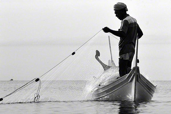 Ein Fischer holt sein Fischernetz ein.