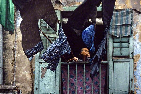 Eine alte Frau steht in Hongkong auf einem Balkon und raucht. Vor ihr trocknen Wäschestücke.