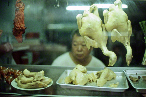 Eine Frau steht hinter zwei toten und gehäuteten Hühnchen, die im Schaufenster hängen.