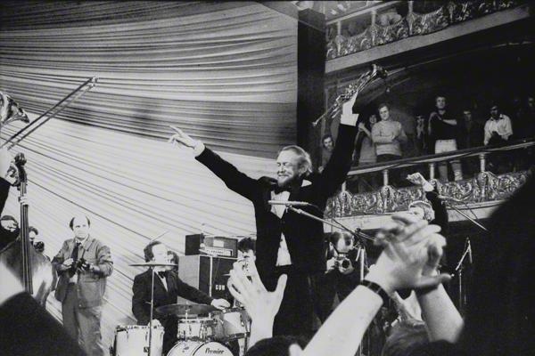 Bob Wallis aus Großbritannien bei einem Konzert mit seinem Orchester im Rahmen des Jazzfestivals in Prag im Oktober 1971. Im Vordergrund klatschendes Publikum. Hinter den Musikern Zuschauer auf den Rängen.