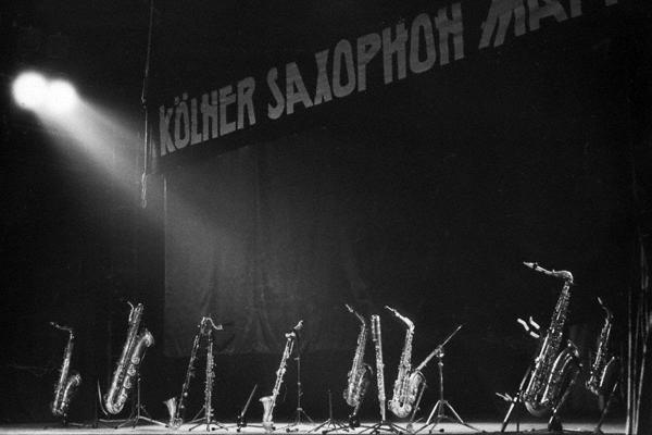 """Die Saxofone der Jazzband """"Kölner Saxophon Mafia"""" stehen in ihren Ständen auf der Bühne des Jugendklubhauses in Halle an der Saale im März 1990 für die Musiker bereit. Im Hintergrund auf dem Vorhang der Name der Band. Die Instrumente werden von einem Scheinwerfer angestrahlt."""