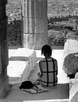 Eine Touristin sitzt im Schatten einer Säule der Akropolis und blickt auf die Stadtlandschaft von Athen.