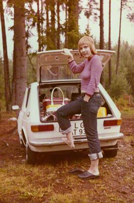 Eine Frau steht während ihrer Urlaubsreise am vollgepackten Auto.