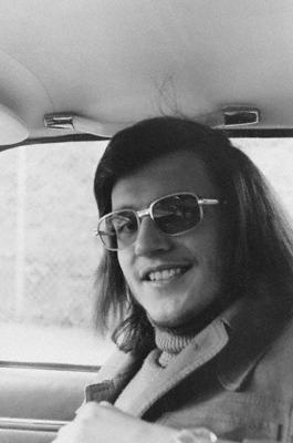 Ein Mann mit Vokuhila und Sonnenbrille sitzt in einem Auto.