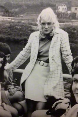 Eine modisch gekleidete junge Frau während eines Schulausflugs auf einem Boot.