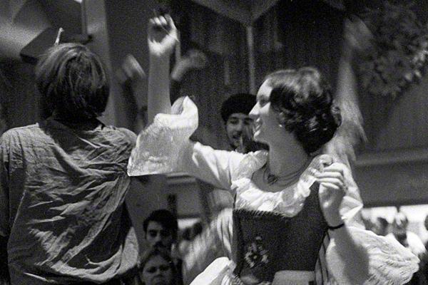 Eine Frau in Dirndl tanzt auf dem Tisch in einem Festzelt.