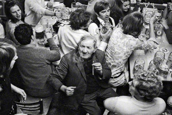 Ein älterer Mann raucht eine Zigarre inmitten von feiernden Menschen mit Bierkrügen in einem Festzelt auf dem Münchner Oktoberfest.