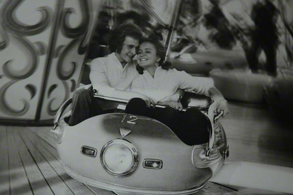 Ein junges Paar fährt Autoscooter auf dem Oktoberfest.