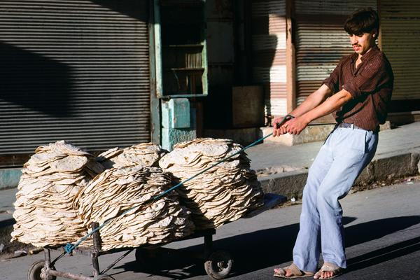 Ein Mann zieht Fladenbrot auf einem Karren hinter sich her.
