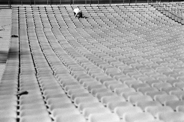 Ein einzelner Arbeiter montiert die Sitze im Münchner Olympiastadion.