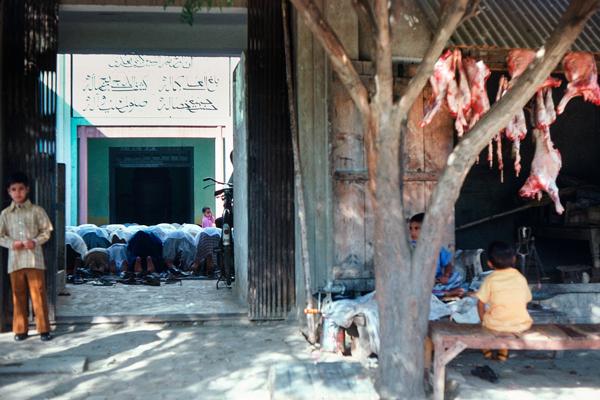 """Während in der Moschee gebetet wird, ist der Metzgerladen neben dem Eingang verwaist, nur Kinder """"bewachen"""" ihn"""