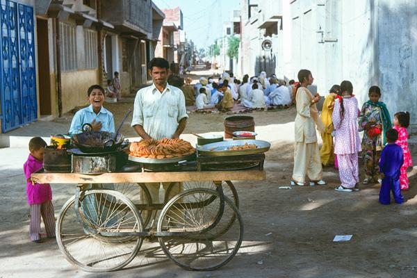 Während die Gläubigen beten, hat sich der Zuckerbäcker schon positioniert. Auch die jungen Mädchen sind voller Vorfreude.