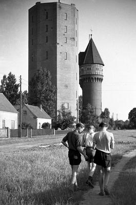 Drei junge Männer einer Fotogruppe der Oberschule Fürstenwalde auf einem Ausflug an einem Turm.