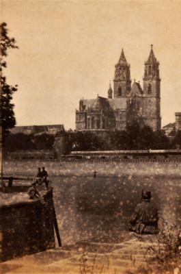 """Das Magdeburger Original """"Schlackaffe"""" sitzt auf seinem Lieblingsplatz um 1865 an der Elbe in Magdeburg, Kleiner Stadtmarsch,an der ehemaligen Schleuse mit Blick auf den Dom. Fotografiert um 1865 vom französischen Fotografen Adolphe Braun (1812-1877)."""