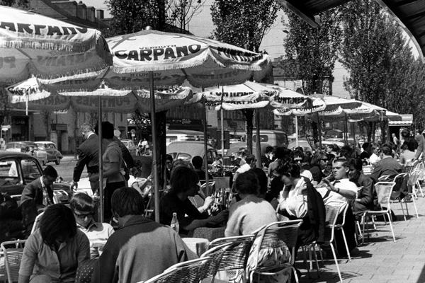 Gäste sitzen an Tischen eines Cafés in der Leopoldstraße in München an einem sonnigen Tag.