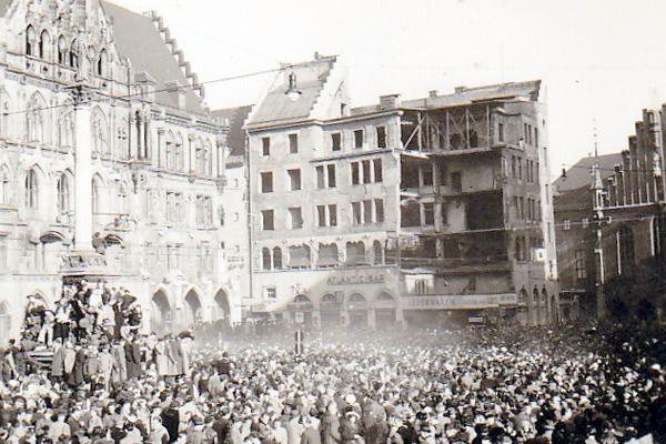 Eine dicht gedrängte Menschenmenge, die sich anlässlich der Faschingsfeierlichkeiten um die Mariensäule auf dem Marienplatz versammelt hat.