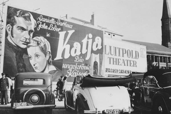 """Das Luitpold-Theater wirbt mit einer großflächigen Anzeige für den Film """"Katja - Die ungekrönte Kaiserin"""". Im Vordergrund stehen Autos mit dem für die amerikanische Besatzungszone typischen """"AB""""-Kennzeichen. Rechts im Hintergrund sieht man die Griechisch-Orthodoxe Salvatorkirche."""