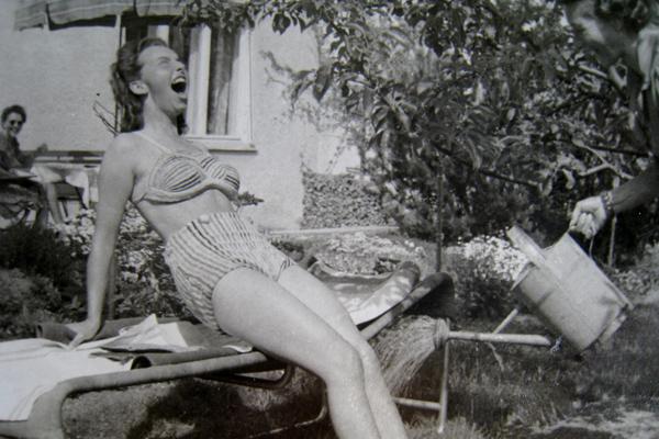 Eine junge, lachende Frau im Bikini wird auf einer Liege im Garten mit Wasser aus einer Gießkanne abgekühlt.