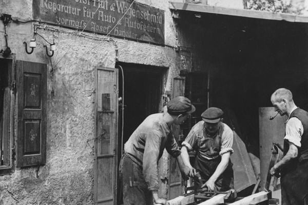 Drei Männer bei der Arbeit in einer Wagenschmiede in München-Au.