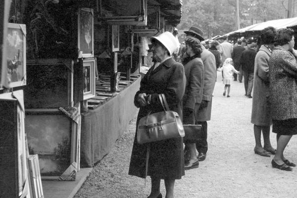Eine alte Frau mit Handtasche betrachtet Gemälde an einem Verkaufsstand auf der Kirchweih-Dult in Au in München.