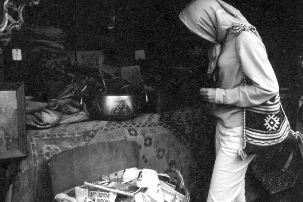 Eine junge Frau mit Kopftuch und Handtasche begutachtet den Trödel an einem Verkaufsstand auf der Auer Dult im Herbst.