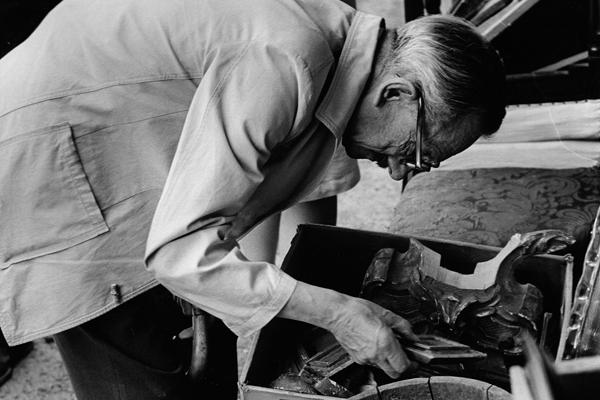 Ein älterer Mann sucht auf der Auer Dult in München nach brauchbarem Trödel.