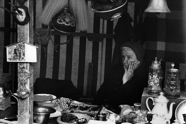 Eine ältere Trödelverkäuferin auf der Auer Dult wartet auf Kundschaft.