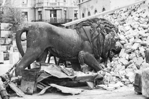 Der bayerische Löwe vom Münchner Siegestor an einem Trümmhaufen lehnend.