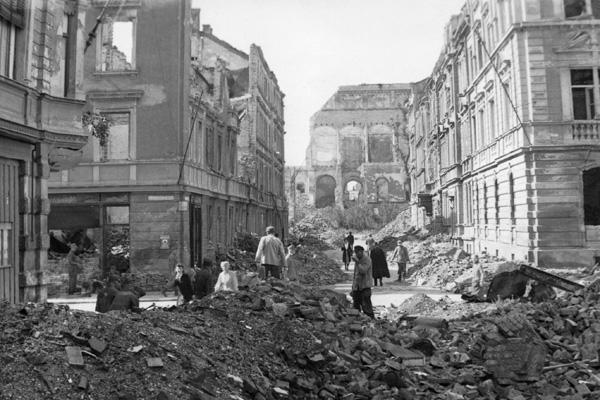 Menschen bei der Trümmerbeseitigung nach einem alliierten Bombenangriff im Frühjahr 1945 an der Kreuzung Schellingstraße Schraudolphstraße in Schwabing. Im Hintergrund die zerstörte Neue Pinakothek.