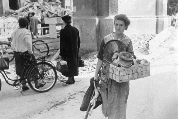 Am Morgen nach der Bombennacht im Sommer 1944 in München bringt eine Frau Dinge aus ihrem Haus in Sicherheit, darunter ein Kruzifix.