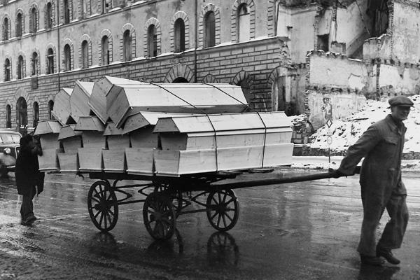 Zwei Männer transportieren neu hergestellte Särge auf einem Handwagen durch die Straßen Münchens. Die Särge sind für dei möglichen Opfer, die der harte und kalte Winter im kriegszerstörten München bringen kann, bestimmt.