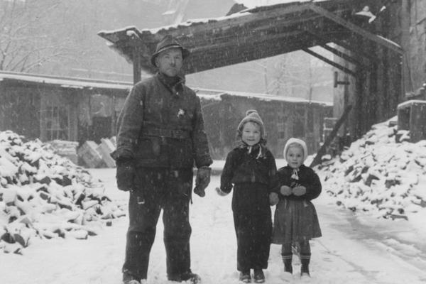 Ein Vater mit seinen beiden Kindern in einem Innenhof, in dem noch Berge von Schutt liegen.