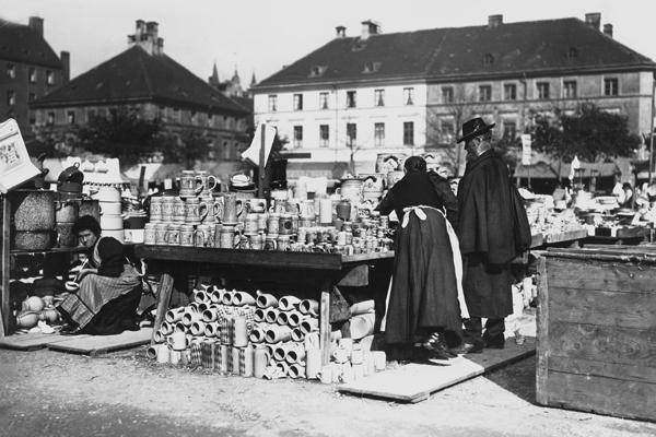 Blick auf einen Stand auf dem Markt, der alle Arten von Tonkrügen und Tontöpfen verkauft. Eine Verkäuferin berät einen Herrn (undatierte Aufnahme).