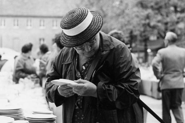 Eine alte Frau sieht sich auf der Münchner Auer Dult auf dem Mariahilfplatz angebotenes Geschirr an.