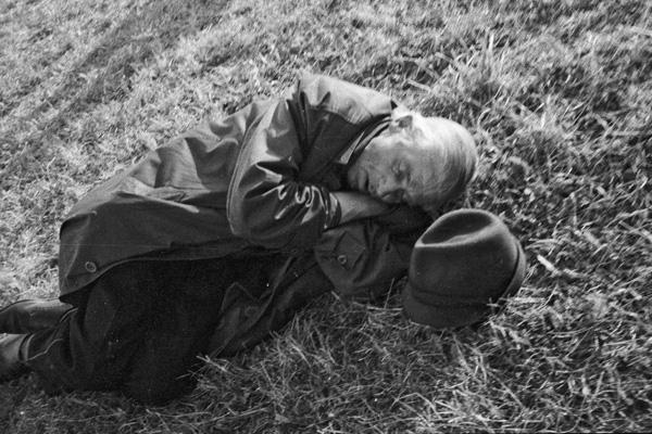 Ein älterer Mann schläft auf einer Wiese neben seinem Hut auf dem Münchner Oktoberfest.