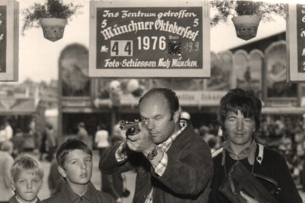 Kinder schauen ihrem Vater beim Schießen an einer Schießbude auf dem Münchner Oktoberfest zu.