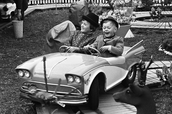 Zwei lachende Kinder im Auto eines Fahrgeschäftes auf dem Oktoberfest in München.