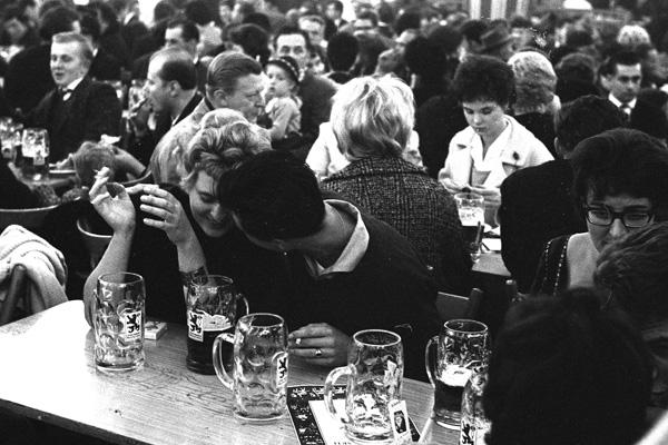 Ein junges Liebespaar an einem Tisch in einem Bierzelt auf der Theresienwiese in München.