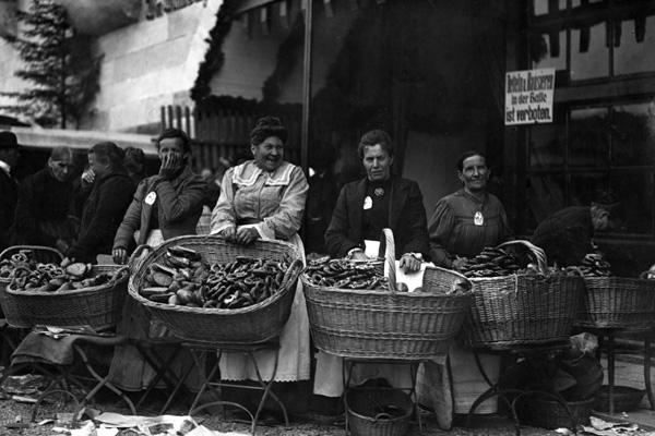 1920-1939 Historisch, Oktoberfest, Vor einem Bierzelt bieten Frauen Brezeln zum Verkauf an.