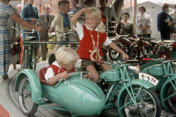 Zwei Kinder auf einem Motorrad mit Beiwagen auf dem Kinderkarussell, Oktoberfest 1959.