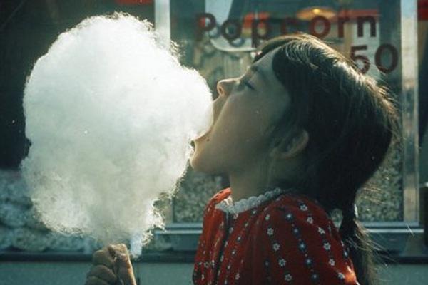 Ein kleines Mädchen beißt genüßlich in eine riesige Zuckerwatte auf dem Oktoberfest.