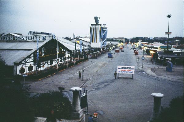 """Leere Gassen und Fahrgeschäfte auf dem Oktoberfest-Gelände am Tag nach dem Attentat vom 26.09.1980. Auf dem Schild steht """"Heute geschlossen"""", """"Closed today"""" und """"Aujourd'hui fermé""""."""