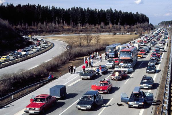 Menschen stehen während eines Staus neben ihren Fahrzeugen auf der Autobahn A99 in Richtung Süden bei der Ausfahrt Haar bei München.