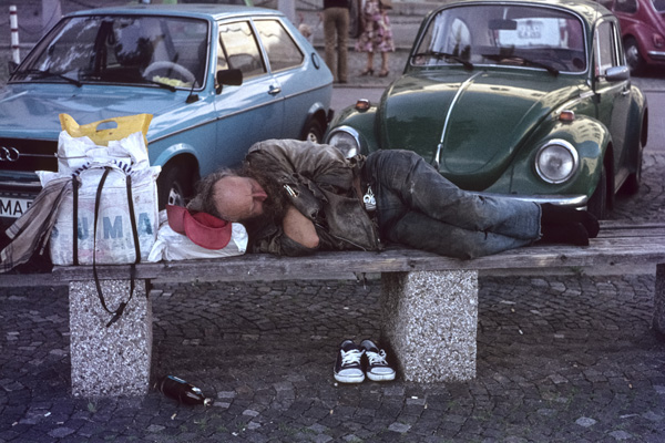 Ein Obdachloser schläft auf einer Bank vor der Münchner Universität in Schwabing