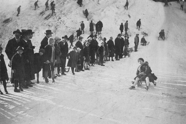 Eine Frau und ein Kind fahren auf einem Schlitten einen Hang auf der Theresienwiese in München hinab.