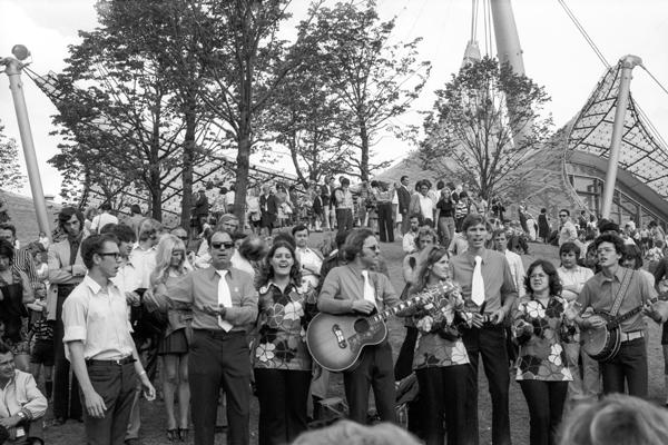 Besucher der Olympiaparks während den Olympischen Spielen. Eine Gruppe von Sängern singt Lieder.