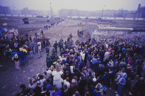 Eine Menschenmenge steht vor einem mit Graffiti bemalten Mauerstück beobachtet die Öffnung der Grenze für den Autoverkehr am Potsdamer Platz am 12. November 1989.